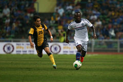 Victor Moses. SHAH ALAM - JULY 21: Chelsea Football Club player Victor Moses (white jersey) dribbles past Nazmi Mansor (25) in a friendly match with the Royalty Free Stock Photography