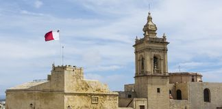 Cathedral and flag of Malta. Victoria also known among the native Maltese as Rabat on island Gozo. View from Citadel to baroque Cathedral and flag of Malta Royalty Free Stock Image