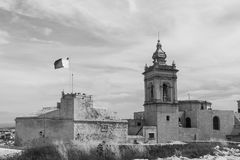 Cathedral and flag of Malta. Victoria also known among the native Maltese as Rabat on island Gozo. View from Citadel to baroque Cathedral and flag of Malta Royalty Free Stock Photography