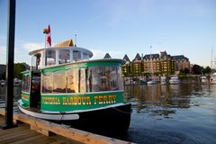 Victoria, BC, Canada harbour ferry with Empress Hotel in Inner Harbour. One of a fleet of harbour taxis - the Victoria Harbour Ferry – pulls into a dock in Stock Photo