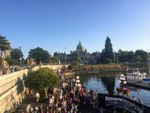 A big group of tourists hanging out on the waterfront along Government Street with the British Columbia Parliament Buildings stock photo