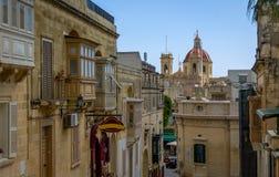 Victoria city street with Saint George Basilica red dome - Victoria, Gozo, Malta. Victoria city street with Saint George Basilica red dome in Victoria, Gozo Stock Photo