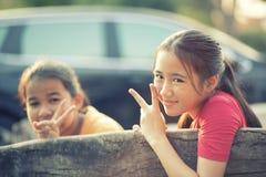 Victoria de la muestra de la mano del adolescente de dos asiáticos con la cara sonriente dentuda Fotos de archivo libres de regalías