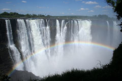 Victoria Falls. The majestic Zambezi river drops in a magnificent thunder in the Victoria Falls as a rainbow forms in the water spray. Taken at Zambezi River royalty free stock image