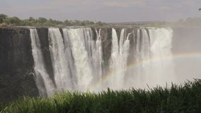 The Victoria falls with mist from water. The Victoria falls is the largest curtain of water in the world (1708 meters wide). The falls and the surrounding area stock video footage