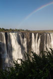 Victoria Falls in October with rainbow crossing Royalty Free Stock Photos