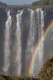 Victoria Falls in Oktober met regenboog kruising Stock Afbeelding