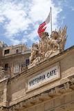 Victoria Gate carvings and Maltese Flag, Valletta, Malta. English Royal crest stone carving seen above Victoria Gate, at the entrance of Valletta from the Grand Stock Image