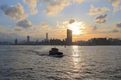 Victoria Harbor av Hong Kong på solnedgången Arkivbilder