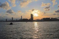 Victoria Harbor av Hong Kong på solnedgången Royaltyfria Bilder