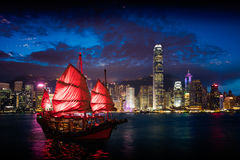 Victoria Harbour. Hong Kong night view with junk ship on foreground stock photo