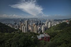 Victoria Harbour in Hong Kong seen from Victoria Peak with hills and a house in the foreground.  stock photography