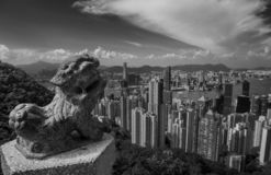 Victoria Harbour in Hong Kong seen from Victoria Peak with the statue of a Chinese lion in the foreground royalty free stock photography