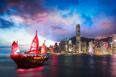 Victoria Harbour. Hong Kong night view with junk ship on foreground royalty free stock image