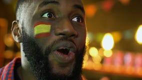 Victoria masculina afroamericana del equipo de fútbol del júbilo de la fan, bandera española en mejilla almacen de video