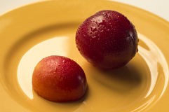 Victoria plum on a yellow plate. Ideal for wallpapers. Could be useful in presentations, web and printing design Stock Photography