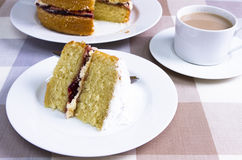 Victoria sandwich. A Victoria sandwich cake served with a cup of tea Stock Photos