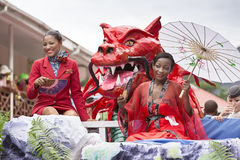 Victoria, Seychelles - February 9, 2013: One women in red dress. Holding white parasol and another in  Air Seychelles uniform floating on platform  on Parade of Stock Photo