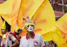 Victoria, Seychelles - February 9, 2013: two men in masques and. Large yellow flags on background walking on Parade of Seychelles international Carnival Stock Photography