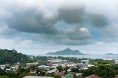VICTORIA, SEYCHELLES - 9 MAGGIO 2013: Landcape dalla montagna dirige verso Victoria ed il porto della città Cielo nuvoloso Immagini Stock Libere da Diritti