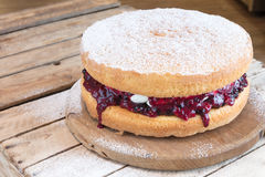 Victoria Sponge Cake with fruit jam filling. Victoria Sponge cake with fruit jam and vanilla cream on rustic wooden cake stand dusted with icing sugar, on wooden stock photo