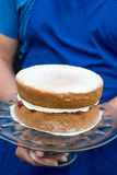 A victoria sponge cake on glass cake stand. A glass cake stand held by person with traditional homemade victoria sponge cake Stock Photo