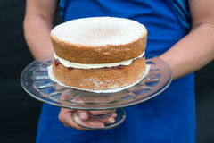 A victoria sponge cake on glass cake stand. A glass cake stand held by person with traditional homemade victoria sponge cake shallow depth of field Stock Photos