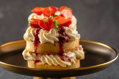Victoria sponge cake with strawberries, jam and whipped cream on dark background. Copy space. stock image
