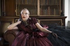 Victoriaanse vrouw in bibliotheek Stock Foto