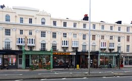 Victorian apartments with small businesses in Hove. Small businesses and shops with cream painted Victorian residential buildings above them on King way in stock image