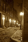 Victorian boston. Sepia toned image of an old 19th Century cobble stone road in Boston Massachusetts, lit only by the gas lamps revealing the shuttered windows Royalty Free Stock Images