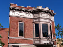 Victorian brick building. Building with red brick lines, large bay windows and stucko decorations. Against dark blue sky Stock Photography