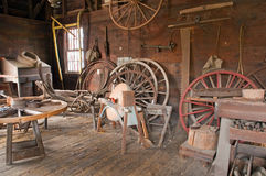 Victorian carriage wheel shop. A view of an antique workshop where vintage Victorian era, horse-drawn carriage wheels were built or repaired.  A person skilled Stock Photos