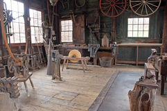 Victorian carriage wheel shop. A view of an antique workshop where vintage Victorian era, horse-drawn carriage wheels were built or repaired.  A person skilled Stock Image