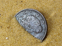 Victorian Coin. Half buried in sand Stock Images