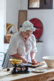 Victorian cook. Staffordshire, England. U.K September - 13 2013 :Young woman dressed in Victorian costume as a domestic cook slicing dates. Staffordshire Royalty Free Stock Photos
