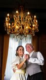 Victorian dance. Victorian scene of two people dancing in a castle, under an antique chandelier Royalty Free Stock Photography