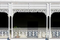 Victorian decorative wrought iron balcony with a plant on it but mostly darkness behind the white painted ornate railings -. Background stock photo