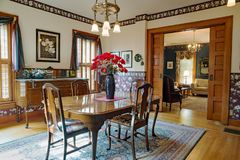 Victorian Dining Room with Pocket Doors. Dayton, Ohio, USA - June 10, 2018: Example of Victorian dining room with flowered wallpaper in burgundy & cream satin royalty free stock photos