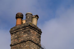 Victorian domestic chimney with four assorted chimney-pots against a clear blue sky background. Copy space Stock Images