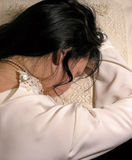 Victorian Drama 2. Brunette woman laying her head on her hands on a pillow. Very sad of crying Royalty Free Stock Photos