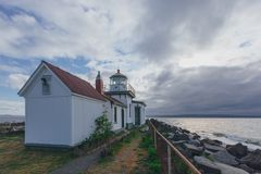 Victorian-era lighthouse under clouds by water in Discovery Park, Seattle, USA stock photos