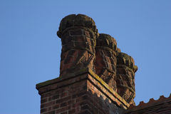Victorian fancy chimney pots. Fancy Victorian chimney pots against a clear blue sky Royalty Free Stock Photos