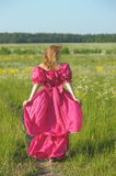 Victorian girl in vintage pink dress back to the camera. Blond in vintage pink dress in the field Royalty Free Stock Images