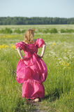 Victorian girl in vintage pink dress back to the camera. Blond in vintage pink dress in the field Stock Photo