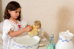 Victorian girl washing doll. Adorable little victorian girl washing her vintage doll Stock Image