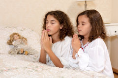 Victorian girls praying. Adorable victorian girls kneeling in their vintage bedroom and praying Royalty Free Stock Images
