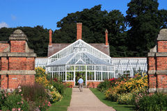 Victorian Greenhouse. A greenhouse is a structure with a glass or plastic roof and frequently glass or plastic walls; it heats up because incoming solar Stock Image