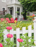 Victorian home with red chairs in summer garden Stock Image