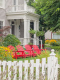 Victorian home with red chairs in summer garden. This historical Victorian home in National Register town of Jacksonville, Oregon has a summer garden with red Stock Photography
